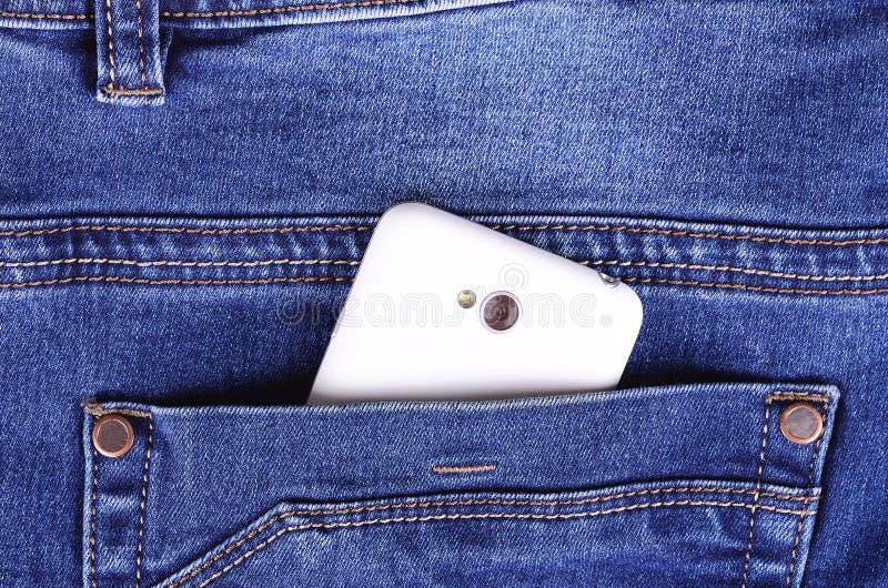 一部分的在蓝色牛仔裤口袋的手机 免版税库存图片