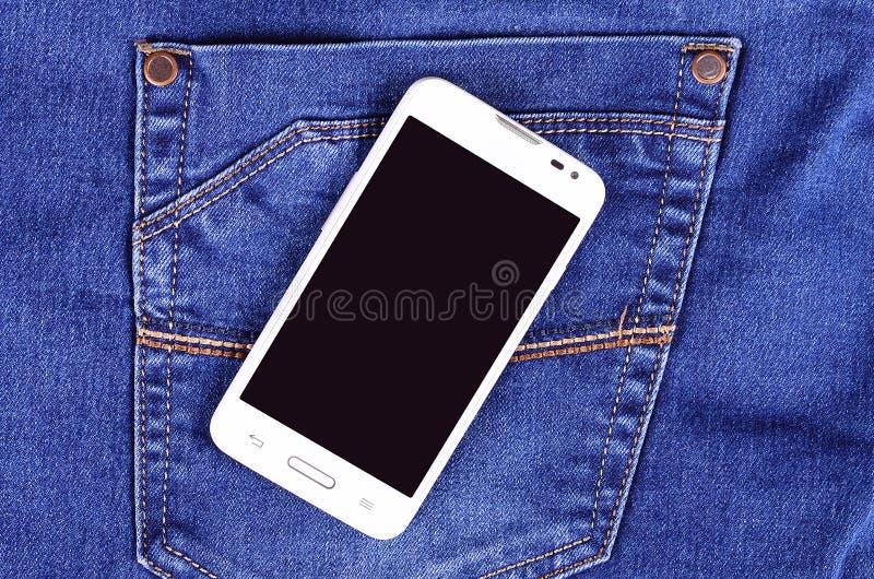 一部分的在蓝色牛仔裤口袋的手机 免版税库存照片