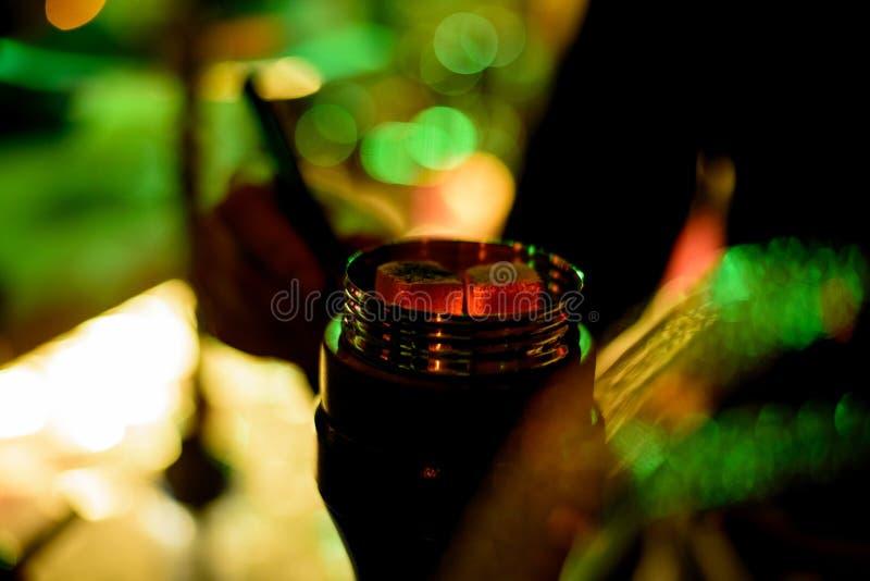 一部分的在shisha碗的水烟筒热的煤炭有黑背景 时髦的东方shisha 五颜六色的射击 免版税库存图片