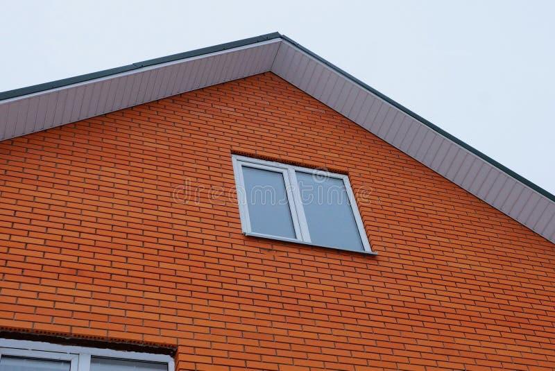 一部分的房子的红砖墙壁有一个白色窗口的反对天空 图库摄影