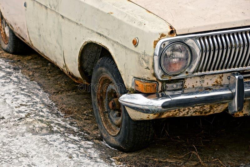 一部分的有一个丰收车灯和一个轮子的一辆老汽车在路地面 免版税库存照片