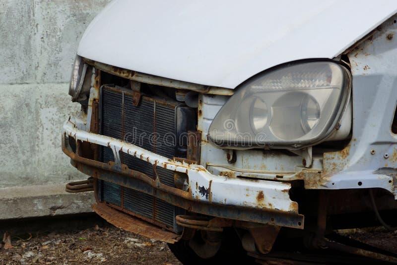 一部分的有一个幅射器和车灯的一辆被碰撞的汽车在街道上 免版税库存图片