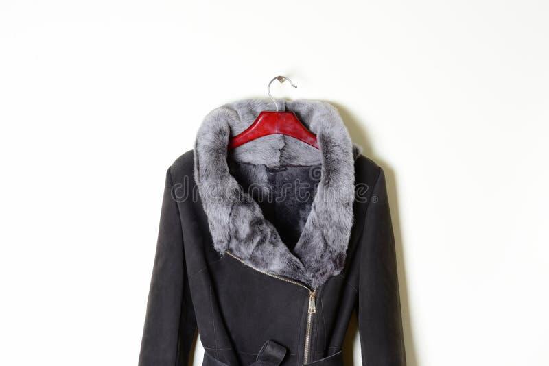 一部分的有一个拉链的一件女性灰色外套,有自然毛皮和传送带衣领的,特写镜头 在挂衣架的紧身连衫外套, 库存图片
