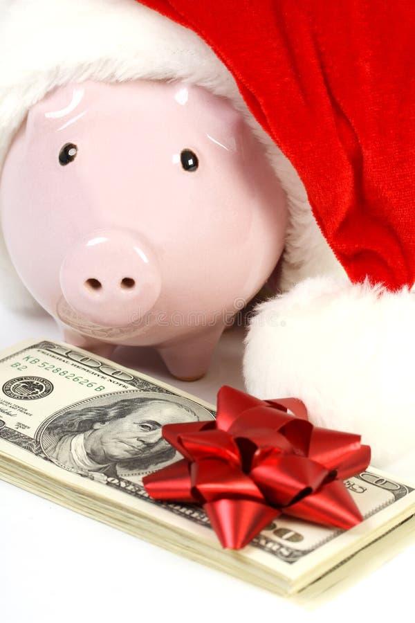 一部分的有圣诞老人帽子的存钱罐和堆金钱美国人与红色弓的一百元钞票 库存照片