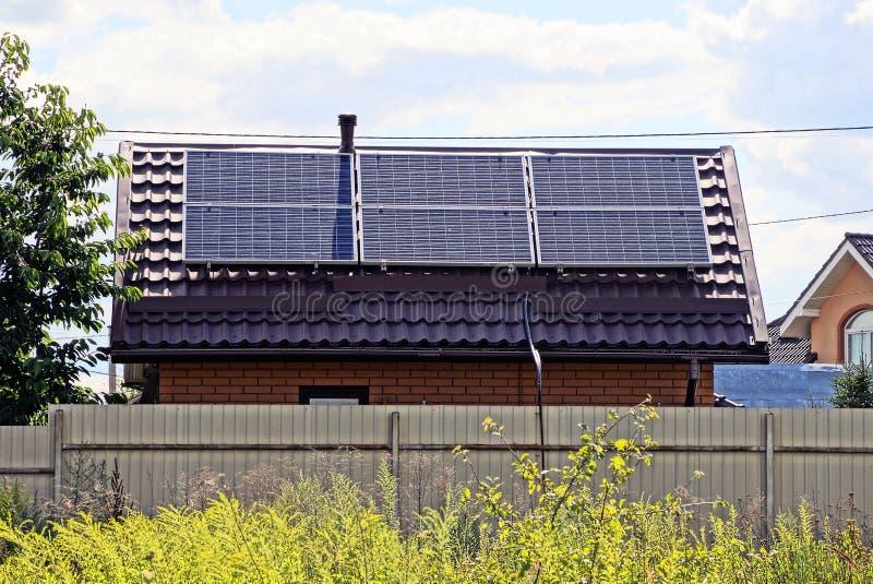 一部分的有太阳电池板的一个棕色房子在铁篱芭后的屋顶在草 免版税库存图片