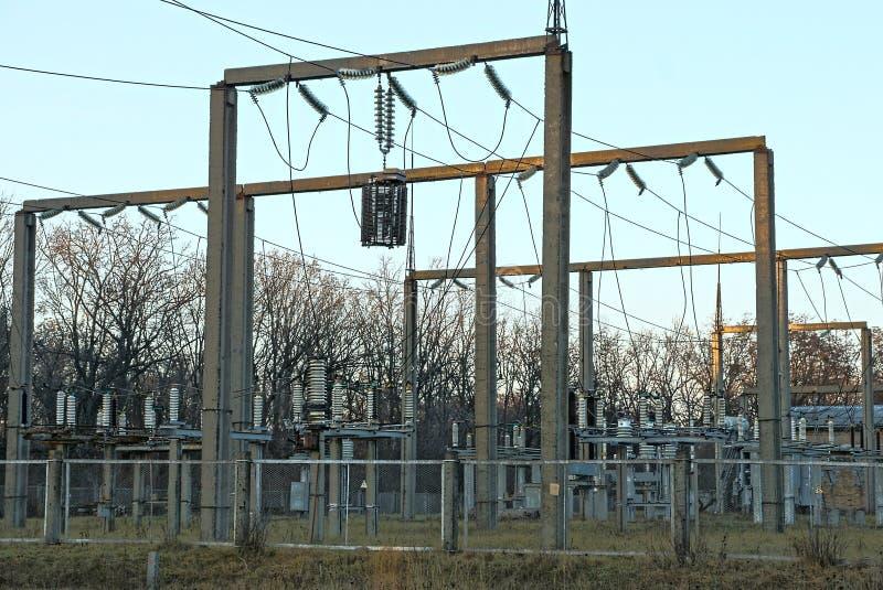 一部分的有杆、变压器和导线的一个能源厂在篱芭后 免版税库存照片