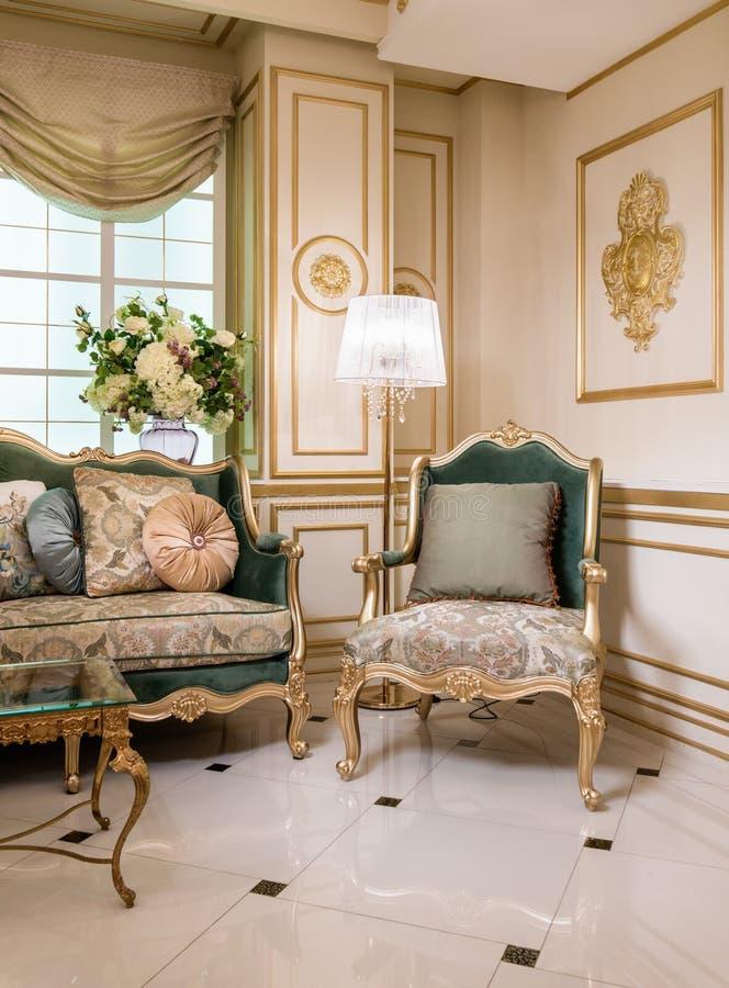 一部分的有沙发和扶手椅子的经典客厅 免版税库存图片