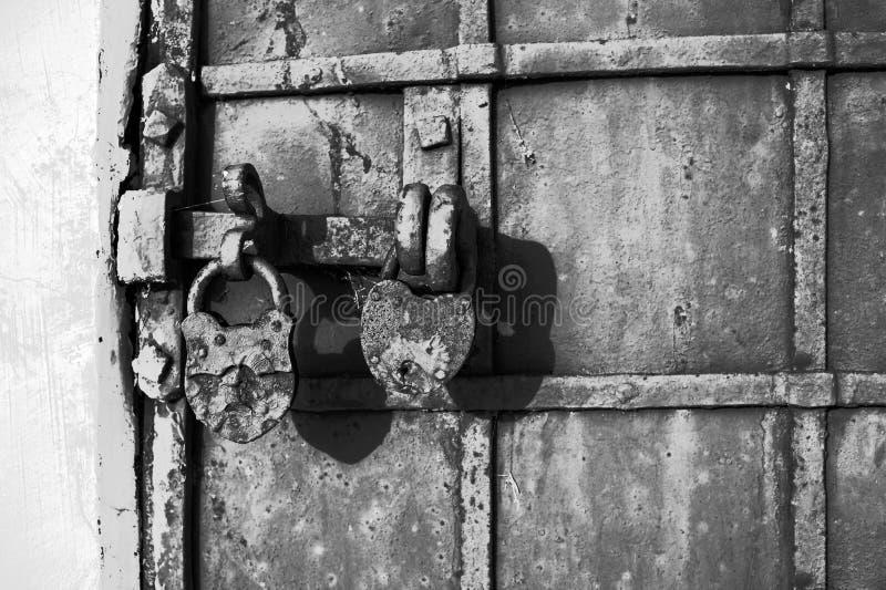 一部分的有门闩和一个老历史建筑的两把锁的一个老金属门 黑白,减速火箭,葡萄酒 免版税图库摄影