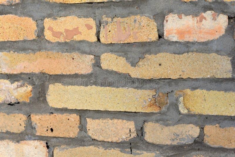 一部分的耐火砖与具体缝的桃子颜色墙壁  图库摄影