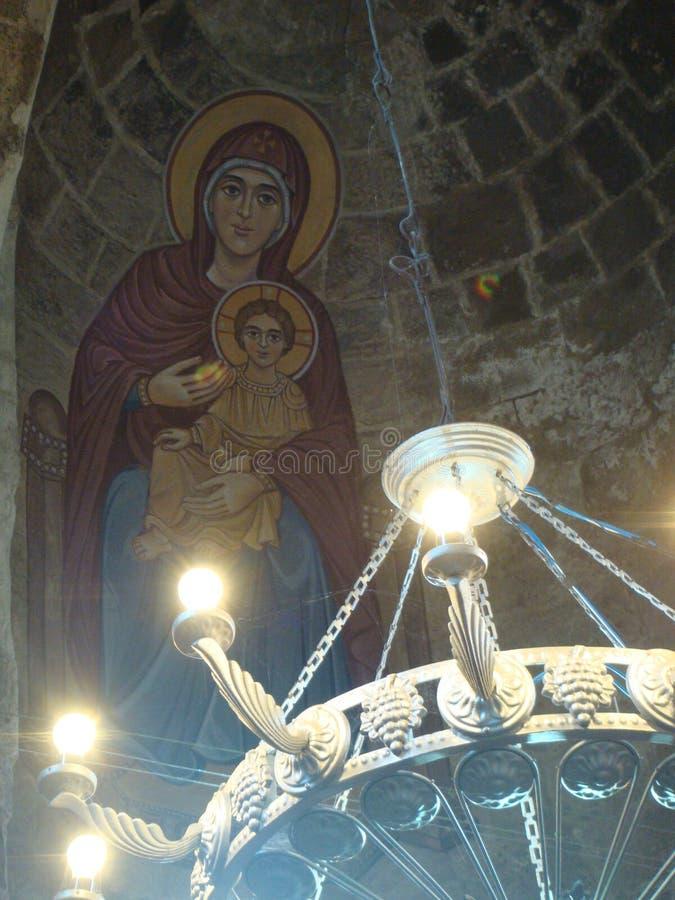 一部分的铁一盏古老枝形吊灯与在天花板的与基督孩子的处女` s剪影在亚美尼亚的修道院里 库存照片