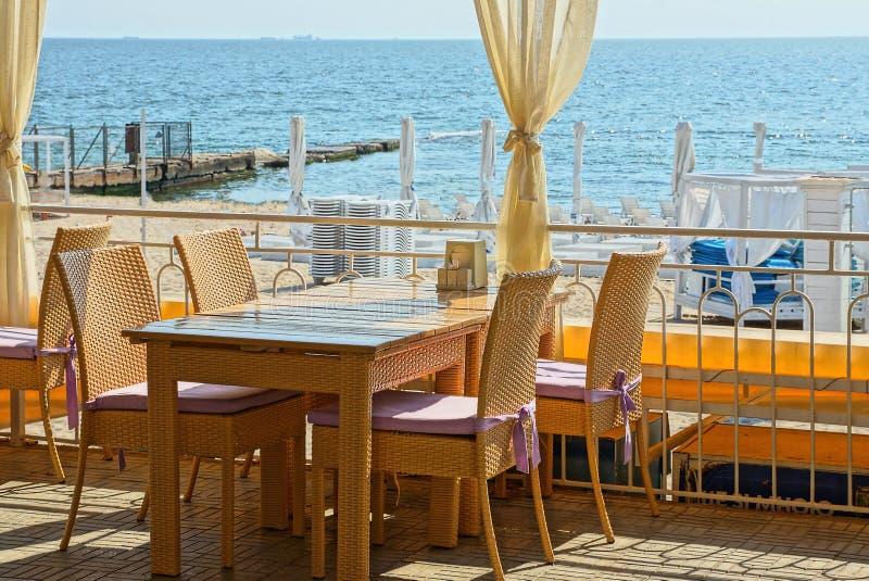 一部分的餐馆和与帷幕的一张桌的夏天大阳台有棕色椅子的在天空和海的背景 免版税图库摄影