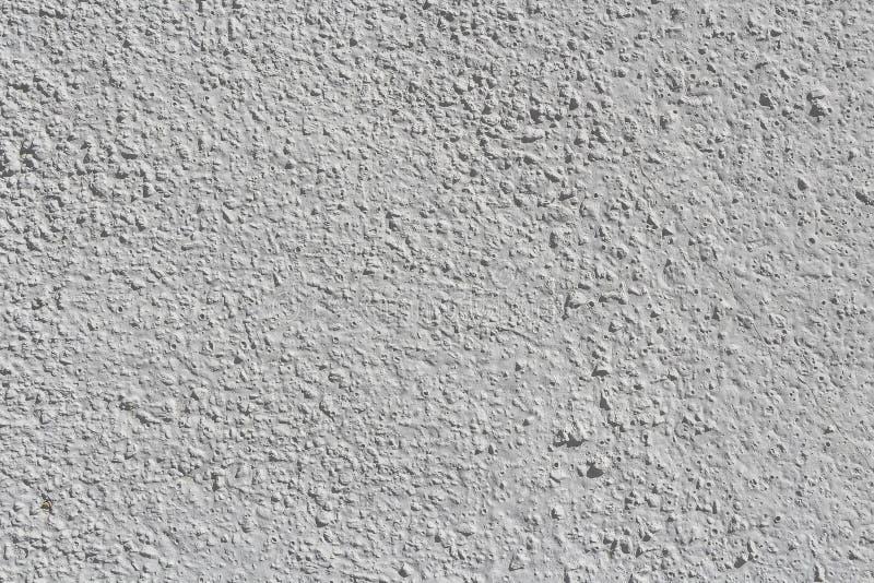 一部分美好的水平的纹理的老混凝土墙绘在灰色和白色和与在照片的孔 免版税库存图片