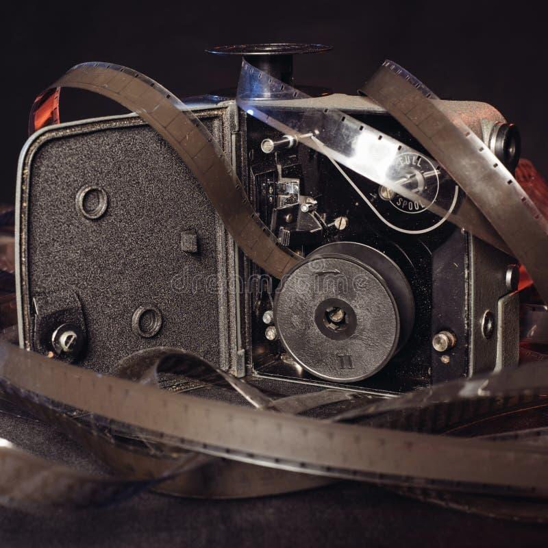 一部老影片的特写镜头和葡萄酒电影摄影机的里面在桌上的 库存图片