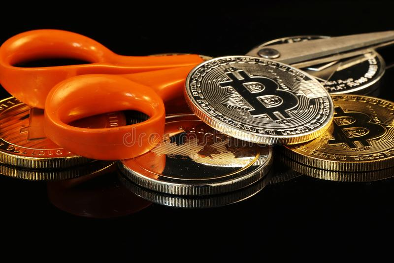 一银色bitcoin在与剪刀和其他cryptocurrency的中心 图库摄影