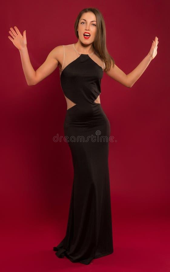 一长黑礼服摆在的美丽的女孩 免版税库存照片
