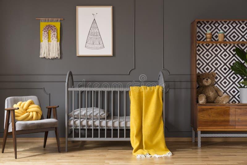 一间婴孩屋子的真正的照片有站立在ar之间的黄色轻便小床的 库存图片