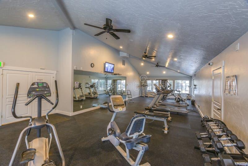 一间宽敞健身健身房的内部与各种各样的运动器材的 库存图片