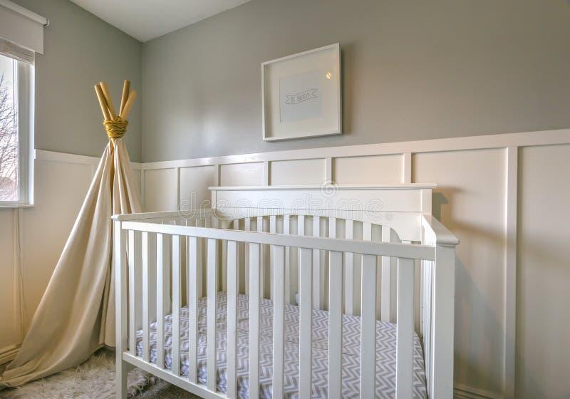 一间屋子的内部孩子的有白色木小儿床和戏剧圆锥形帐蓬的 图库摄影