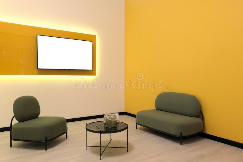 一间现代高科技屋子的Minimalistic室内设计 r 在电视屏幕上的白色拷贝空间在墙壁上 黄色LED光 免版税图库摄影