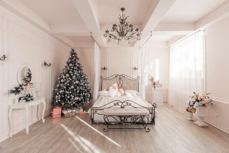 一间轻的屋子的古典内部 早晨在卧室 与一个白色壁炉的经典公寓,装饰的圣诞节 免版税库存图片