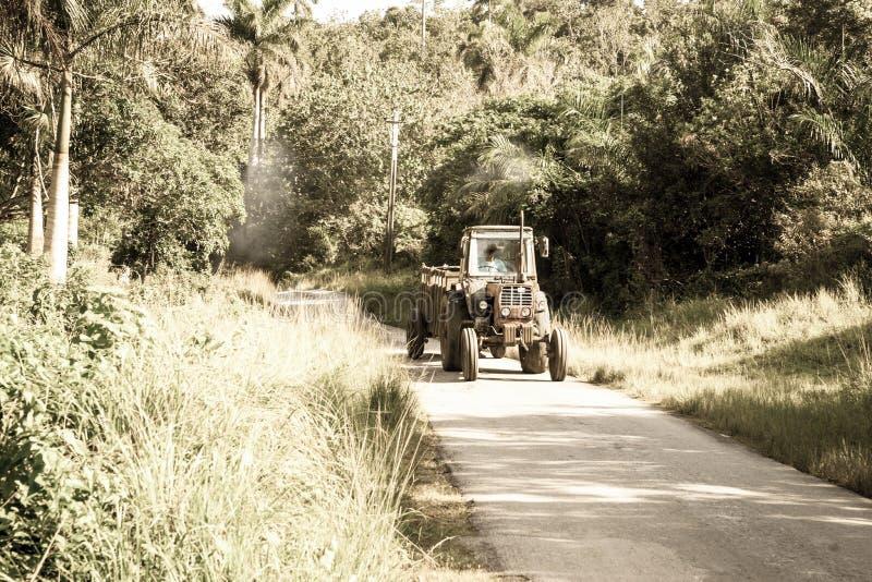 一阵烟幕跟随典型地沿狭窄的农村r的老拖拉机 库存照片