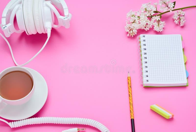 一面少年儿童,铅笔笔记本橡皮擦花饮料玻璃的构成的桌的顶视图与耳机的在桃红色 图库摄影