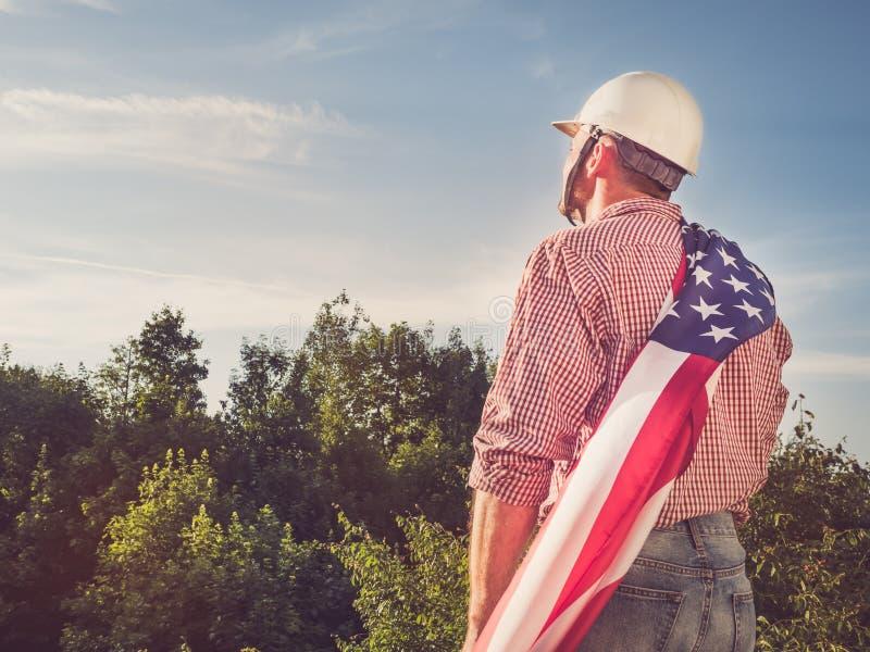 一面白色盔甲和美国国旗的工程师 免版税库存图片