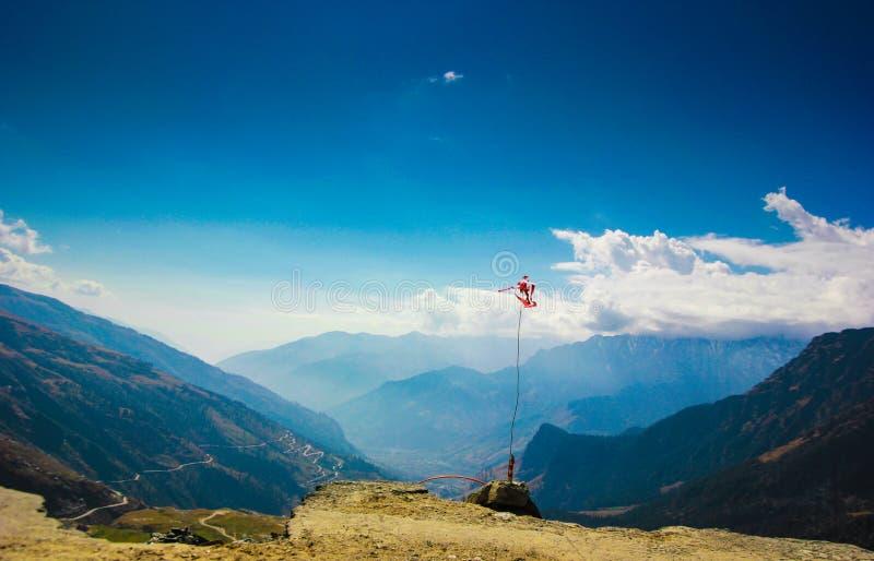 一面红旗,圣洁标志在喜马拉雅山的背景中有蓝天的在manali, himlachal印度 免版税库存照片