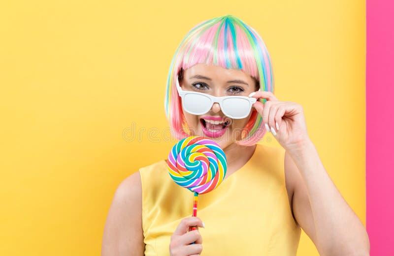 一顶五颜六色的假发的妇女与棒棒糖 免版税库存照片