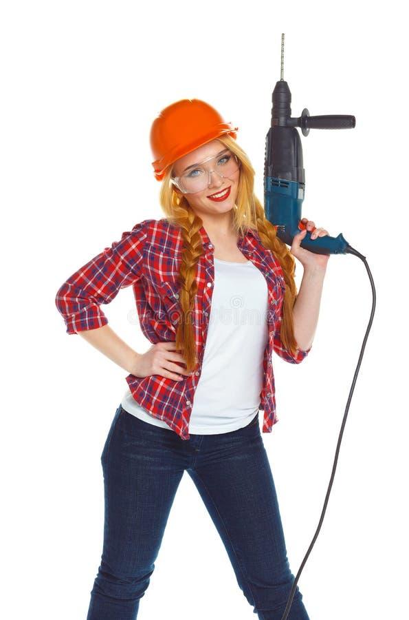 一顶安全帽的女性建筑工人有穿孔器的 免版税图库摄影