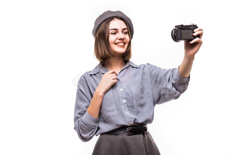 一顶愉快的妇女博客作者佩带的贝雷帽的画象与照相机讲话,当记录录影被隔绝在白色背景时 库存照片