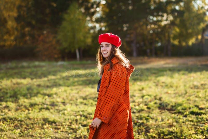 一顶红色贝雷帽的微笑的愉快的女孩青少年 免版税库存图片