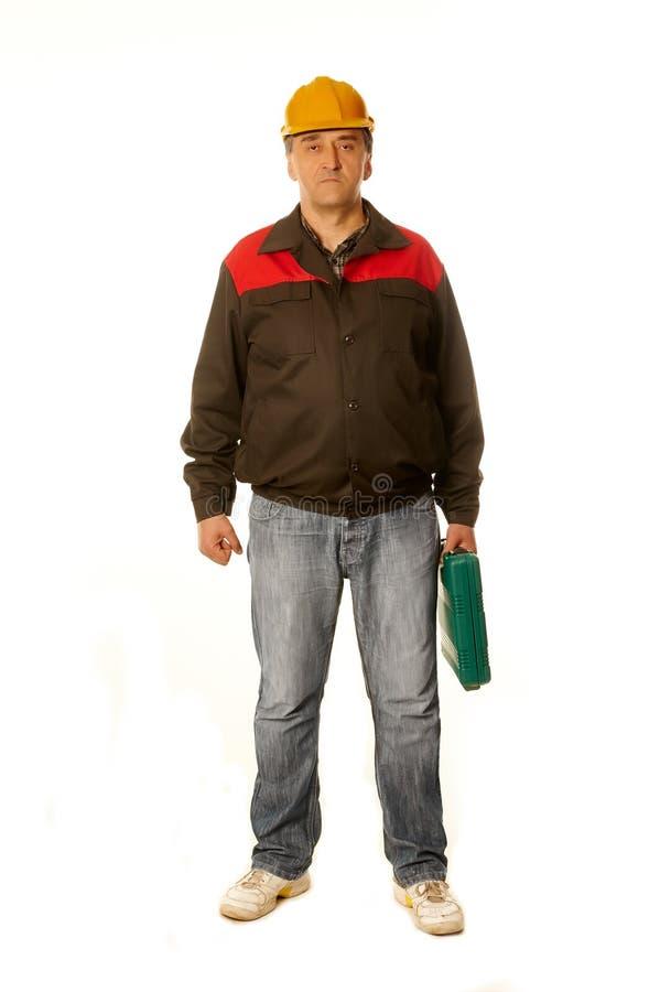 一顶黄色安全帽的工作者带着一个绿色手提箱 免版税库存照片