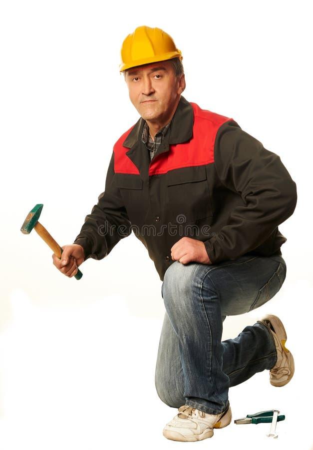 一顶黄色安全帽的工作者蹲下了与锤子,板钳, plie 库存照片