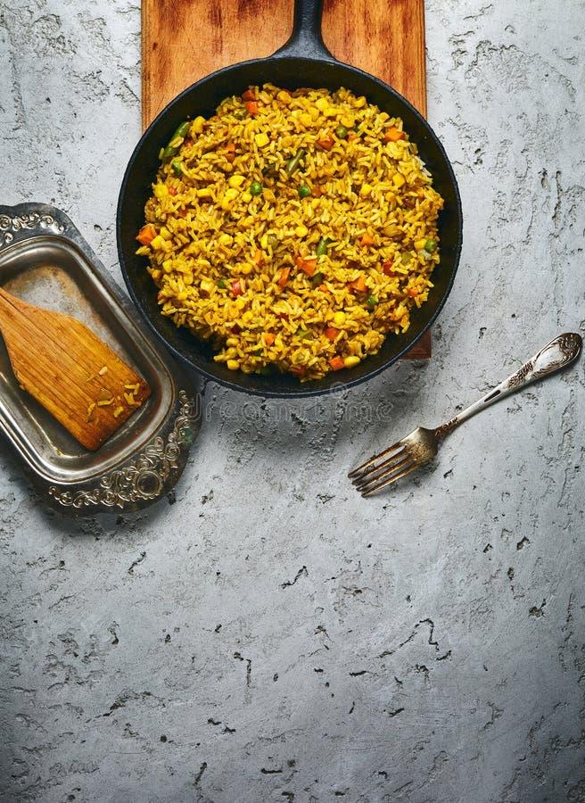 一顿意大利煨饭的顶视图与菜和素食主义者甜菜炸肉排的在一个灰色具体背景的一个黑铸铁煎锅服务 免版税库存照片