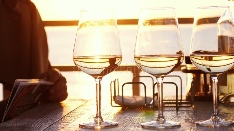 一顿浪漫晚餐在一个海滩的夏天在与三杯的日落白葡萄酒和一个瓶由海的酒 图库摄影