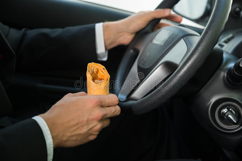 一顿男性举行的快餐的特写镜头,当驾驶时 图库摄影