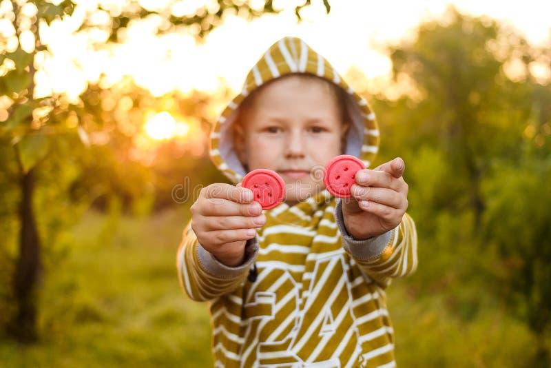 一黄色有冠乌鸦的一个男孩拿着在美好的光的两个曲奇饼 免版税库存照片