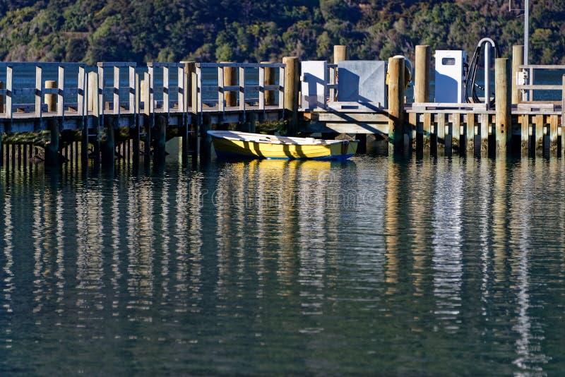 一黄色灰溜溜被栓由在马尔伯勒的一个码头决定听起来,新西兰 免版税库存图片