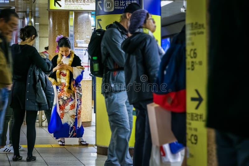 一件传统冬天和服礼服的日本妇女在地铁站 免版税库存照片