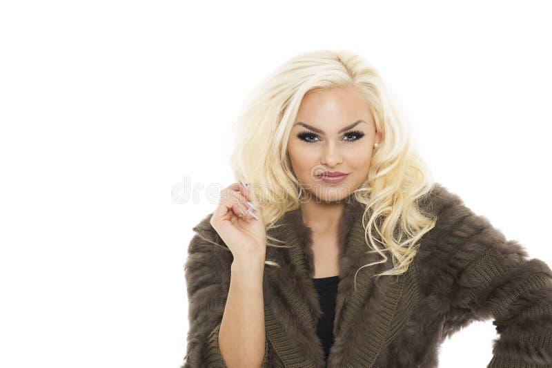 一件典雅的冬天球衣的可爱的白肤金发的妇女 库存图片