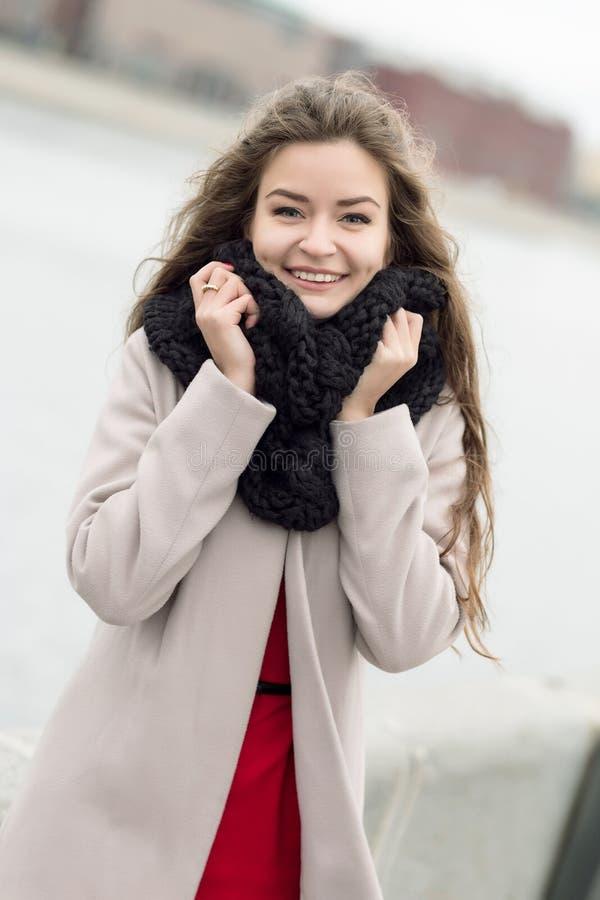 一件外套的少妇在街道上微笑对照相机的 一件黑外套、一条围巾和一件红色礼服的女孩反对灰色天空 不是我 库存照片