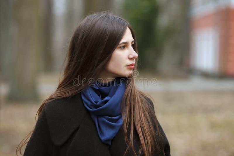 一件黑外套的年轻美丽的女孩和步行的蓝色围巾在秋天/春天停放 有华美的一个典雅的深色的女孩 免版税库存照片