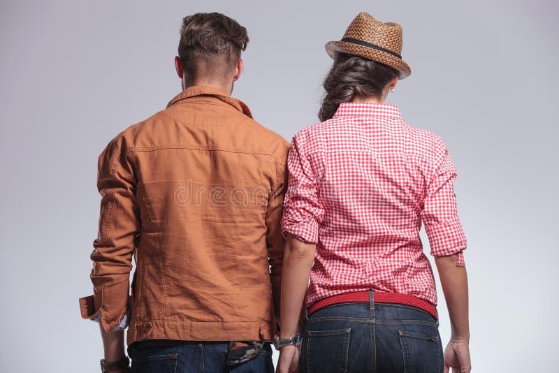 一年轻夫妇摆在的背面图 免版税库存照片