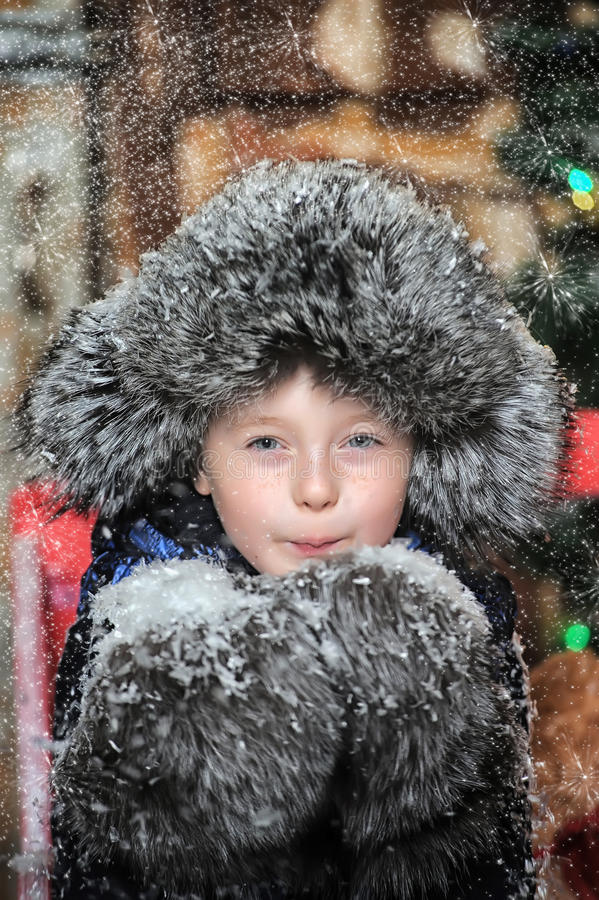 一件夹克和一顶裘皮帽的男孩在与雪花的圣诞节 库存图片