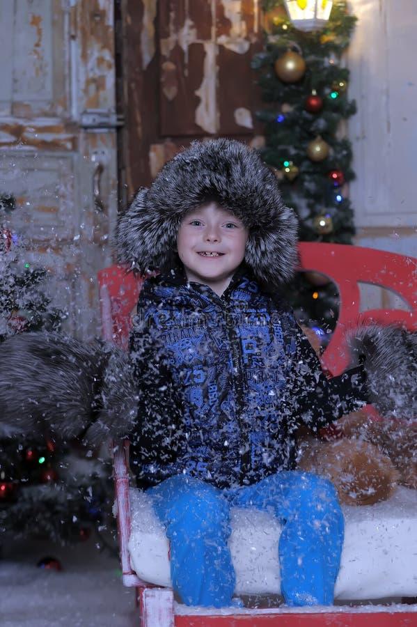 一件夹克和一顶裘皮帽的男孩在与雪花的圣诞节 库存照片