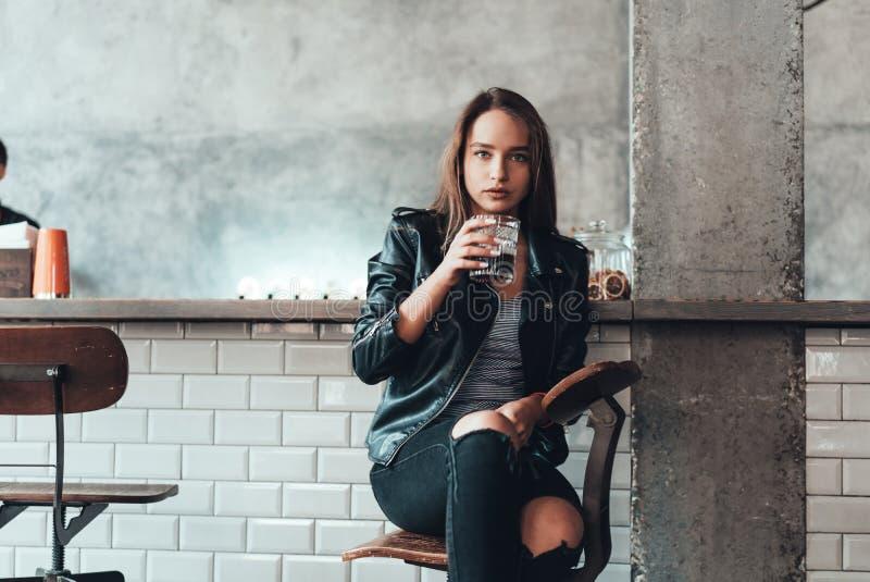 一件黑夹克的美丽的女孩在咖啡馆 免版税库存照片