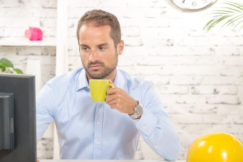 一份年轻工程师饮用的咖啡 免版税库存照片