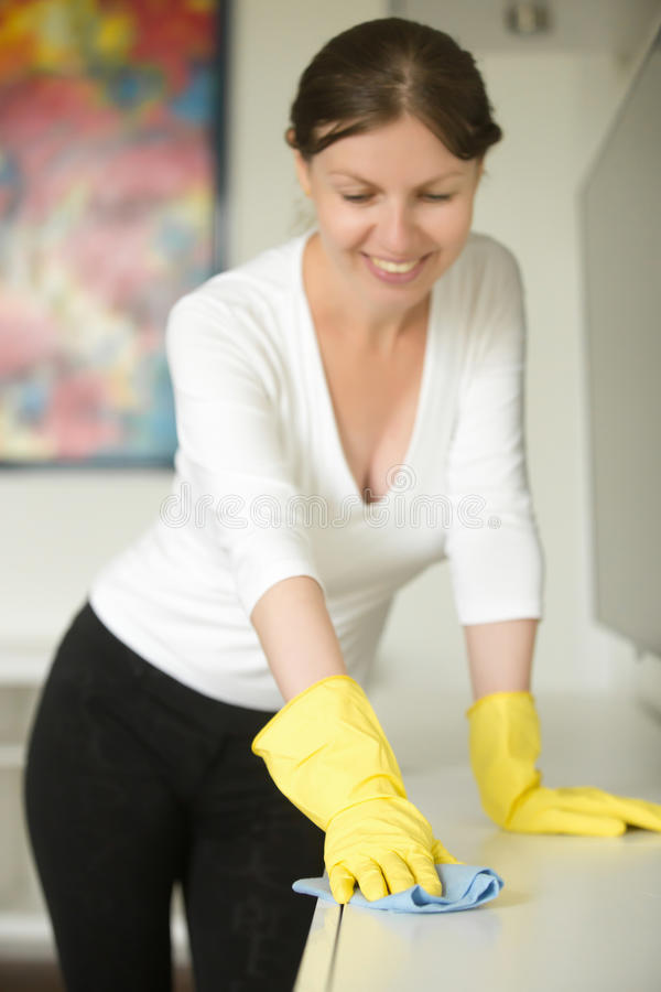 一年轻微笑的妇女佩带的橡胶手套清洗的画象 免版税库存照片