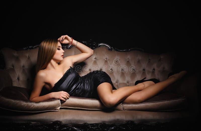 一件性感的黑礼服的美丽的女孩 图库摄影